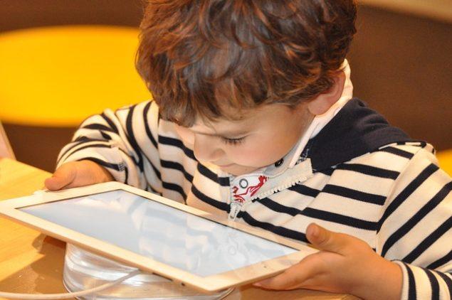 Ein Kind spielt an einem Tablet